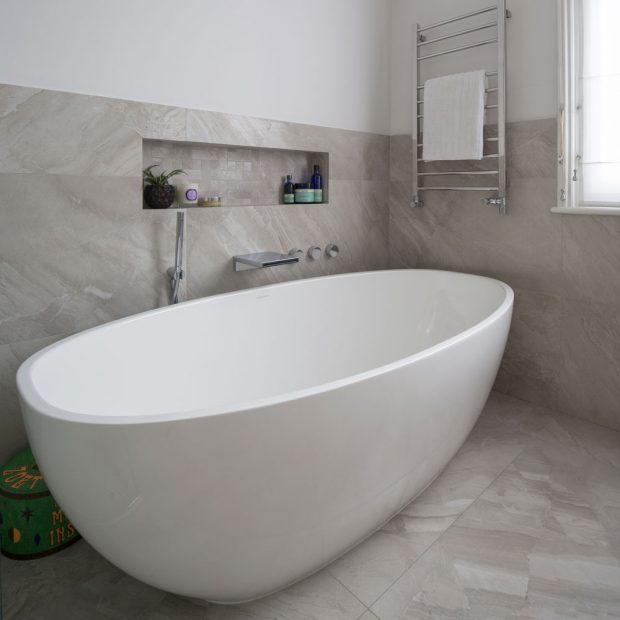 Büyük bağlantısız küvete sahip gri banyo